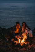 selektivní zaměření pohledný muž uvedení do ohně v blízkosti dívky a řeky