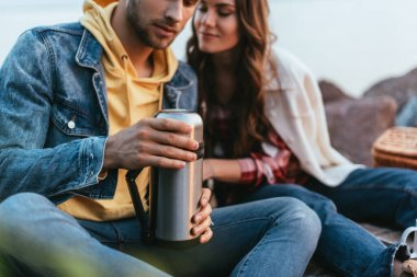Selective focus of bearded man holding thermos beautiful girlfriend stock vector