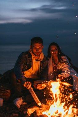 Selective focus of handsome man putting log in bonfire near girl stock vector