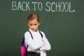 szkeptikus iskolás lány néz kamera közelében vissza az iskola felirat táblán