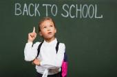 Nachdenkliche Schülerin zeigt Ideengeste, während sie in der Nähe der Tafel mit dem Schulschriftzug nach oben schaut