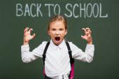 szelektív fókusz dühös iskolás lány mutatja ijesztő gesztus közelében táblán vissza az iskolai betű