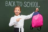 selektivní zaměření usměvavé školačky ukazuje na růžový batoh v blízkosti zpět do školy nápisy na tabuli