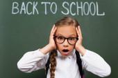 szelektív fókusz sokkos iskolás lány szemüvegben érintő fej közelében vissza az iskolai betű a táblán