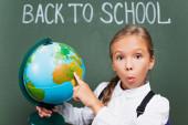 překvapená školačka ukazující prstem na glóbus v blízkosti školní nápisy na tabuli