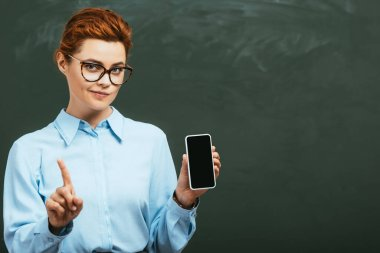 skeptical teacher showing forbidding gesture while holding smartphone with blank screen near chalkboard