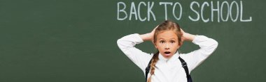 Panoramic shot of shocked schoolgirl touching head near chalkboard with back to school inscription stock vector