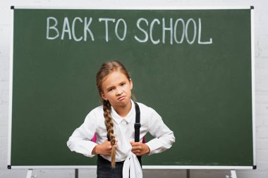 Displeased schoolgirl with heavy backpack near chalkboard with back to school lettering stock vector