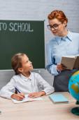 mosolygó tanár nézi iskolás lány ül az asztalnál, és írni notebook
