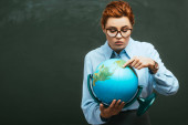 attractive young teacher pointing with finger at globe while standing near chalkboard