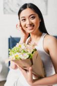 Selektivní zaměření asijské ženy s úsměvem na kameru a držení kytice v ložnici
