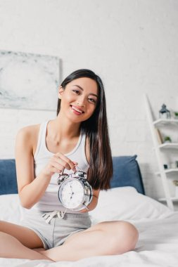 Beautiful asian woman smiling at camera while holding alarm clock on bed at morning stock vector