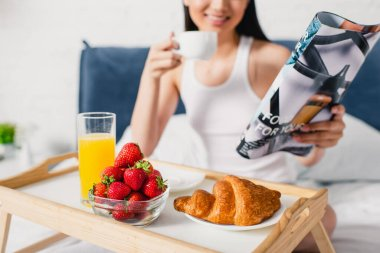 Selective focus of croissant, strawberries and orange juice on breakfast tray and smiling girl holding cup of coffee and magazine on bed stock vector