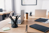 Selective focus of notebooks, stationery and laptops on wooden table in office