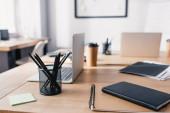Selektivní zaměření notebooků, papírnictví a notebooků na dřevěný stůl v kanceláři