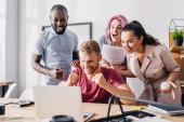 Selektivní zaměření multiethnic business lidé ukazují jo gesto při pohledu na notebook v kanceláři