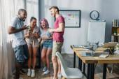 Selektiver Fokus multiethnischer Geschäftsleute mit Gadgets und Kaffee zum Lachen im Büro