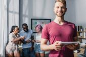 Selektiver Fokus des Geschäftsmannes mit digitalem Tablet und multikulturellen Kollegen im Hintergrund im Büro