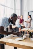 Selektiver Fokus eines afrikanisch-amerikanischen Geschäftsmannes mit Laptop bei der Arbeit in der Nähe multiethnischer Kollegen im Büro
