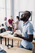Selektivní zaměření afrického amerického podnikatele držícího baseballový míček v blízkosti pizza boxu na stole v kanceláři
