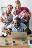 Selective focus of multiethnic business people using laptop together in office