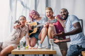 Multicultural business people with acoustic guitar showing peace gesture in office
