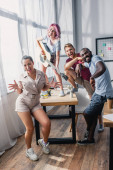 Selective focus of multiethnic business people dancing and playing acoustic guitar in office