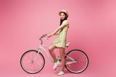 veselý asijské mladý žena v sláma klobouk poblíž kolo na růžový