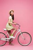 veselá asijské mladá žena v slámě klobouk na koni kolo na růžové