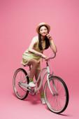 šťastný asijské mladá žena v slámě klobouk na koni kolo a odvrací pohled na růžové