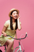 excited asian young woman in straw hat riding bicycle on pink