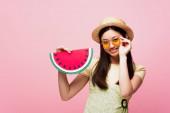 šťastný asijské dívka v slámě klobouk dotýká sluneční brýle a drží papír meloun izolované na růžové