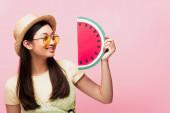 veselé asijské dívka v slunečních brýlích a slamák klobouk při pohledu na papír meloun izolované na růžové