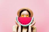 Asijské dívka v slunečních brýlích a slamák pokrývající tvář s papírem meloun izolované na růžové