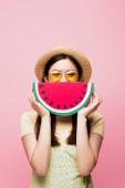 Asijky žena v slunečních brýlích a slamák pokrývající tvář s papírem meloun izolované na růžové