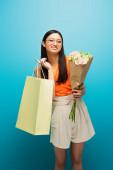 usmívající se asijky žena v brýlích drží nákupní tašku a květiny na modré