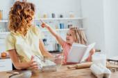 selektivní zaměření dívky držící kuchařku a ukazující prstem na maminku držící skleněnou mísu s whisky