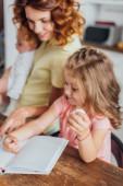 selektivní zaměření matky ukazující prstem na kuchařku, zatímco dcera drží kuřecí vejce