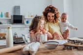 selektivní zaměření mladé matky držící syna a ukazující prstem na kuchařku poblíž dcery, kuchyňské potřeby a ingredience na stole