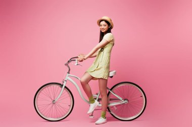 Cheerful asian young woman in straw hat near bicycle on pink stock vector