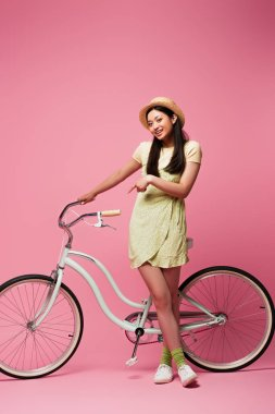 Cheerful asian young woman in straw hat standing near bicycle on pink stock vector