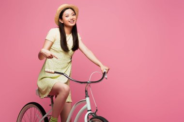 Smiling asian young woman in straw hat riding bicycle isolated on pink stock vector