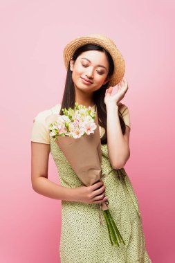 Happy asian girl touching straw hat and holding bouquet of flowers isolated on pink stock vector