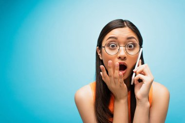 Shocked asian girl in glasses covering mouth while talking on smartphone on blue stock vector