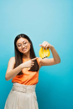 Cheerful asian girl in glasses pointing with finger at ripe bananas isolated on blue stock vector