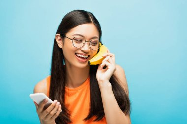 Happy asian girl in glasses using smartphone and holding banana near ear on blue stock vector