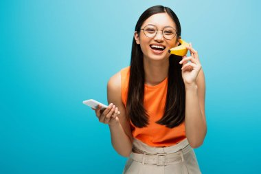 Smiling asian girl in glasses using smartphone and holding banana on blue stock vector