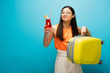 Cheerful asian girl in glasses holding cocktail and baggage while looking away on blue stock vector