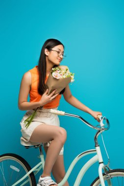 Beautiful asian girl in glasses riding bicycle and holding flowers isolated on blue stock vector