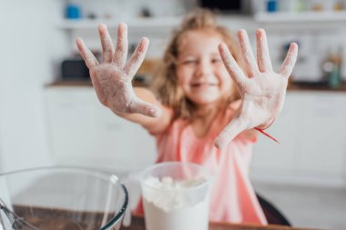 Selective focus of girl showing hands in flour near measuring jug and glass bowl, panoramic shot stock vector